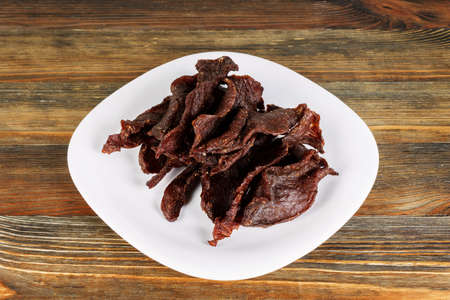 Close-up of beef jerky in a white plate on wood