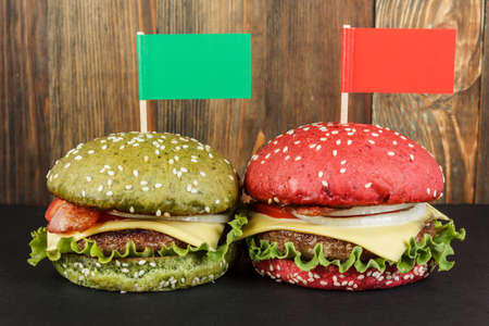 cheeseburgers: Green and red cheeseburgers with flags on wood background close-up Stock Photo