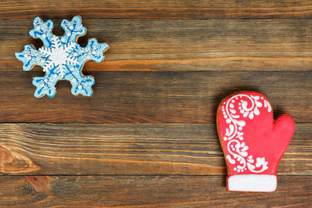 Gingerbread in a shape of a snowflake and mitten on wood background
