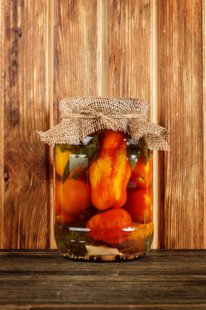 Bank of pickled tomatoes on wood background