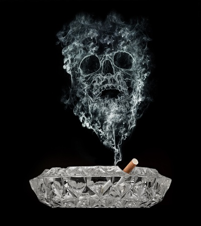 Smoke skull rising from a cigarette. Stock Photo