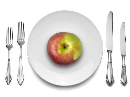 Red apple on white plate with knife and fork, view from top
