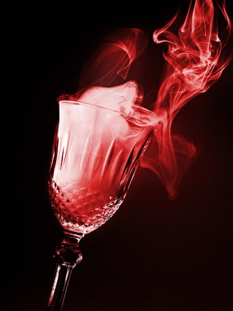glass of magical smoke on black background photo