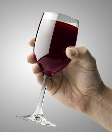 Red wine glass holding by a male hand photo