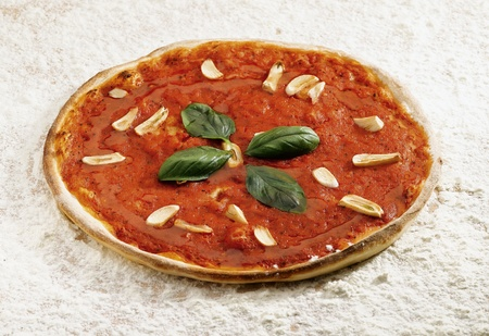 Pizza marinara on a flour background