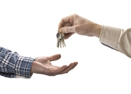 Man is handing a house key to a other man isolated photo