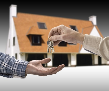 Man is handing a house key to a other man in the shape of the house. photo