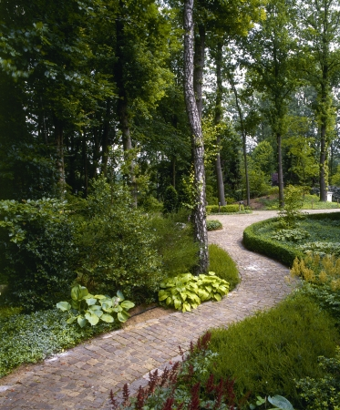 A brick paving stone path through a beautiful garden  Stock Photo
