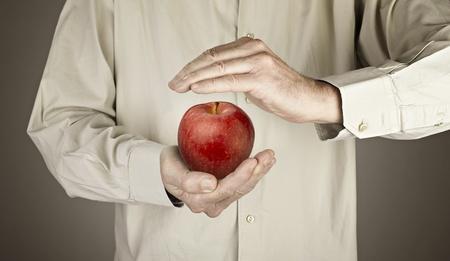 human hands protecting apple Stock Photo - 16432341
