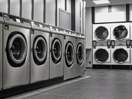 公共のコイン ランドリーで工業用洗濯機の行 写真素材