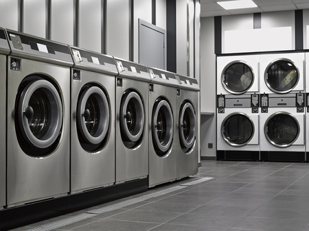 A row of industrial washing machines in a public laundromat Фото со стока