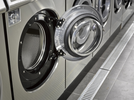 A row of industrial washing machines in a public laundromat Stock Photo