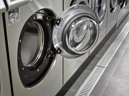 clothes washing: Una fila de lavadoras industriales en una lavander�a p�blica