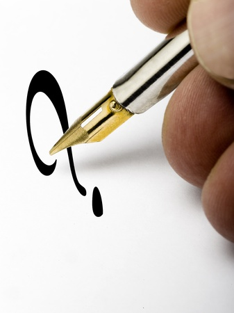 pen writing a question mark on a white page photo