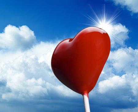 Heart-shaped lollipop on blue sky photo