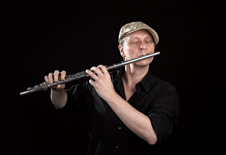 transverse: Portrait of a man playing old silver transverse flute on black background