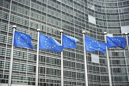 Europäische Flaggen vor dem Berlaymont-Gebäude, dem Sitz der Europäischen Kommission in Brüssel. Lizenzfreie Bilder