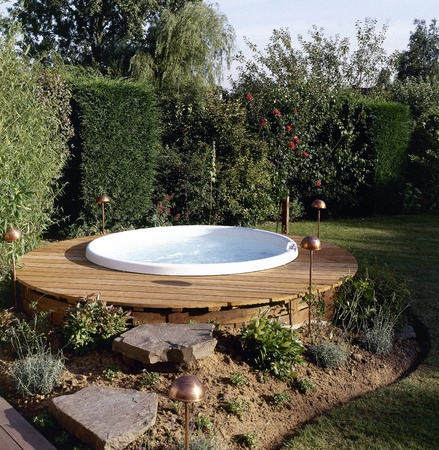 Beautiful outdoor jacuzzi in the backyard garden provides restful relaxation and solitude  Stock Photo