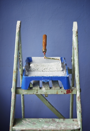 ladder, paint can and paint roller on blue background