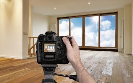 Man fotografeert lege woonkamer met digitale camera Stockfoto
