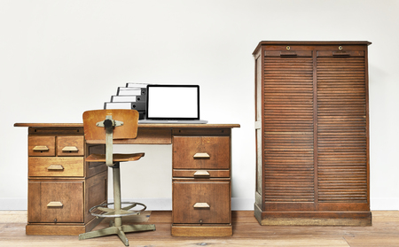 Laptop and folder lying on a vintage desk in a room with wooden floor photo