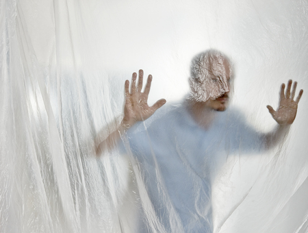 Silhouette of a man behind a transparent plastic Stock Photo - 23810902