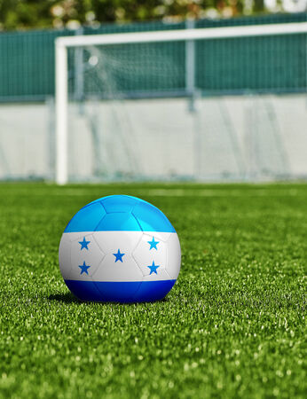 Soccer Ball with Honduras Flag on the grass in stadium photo
