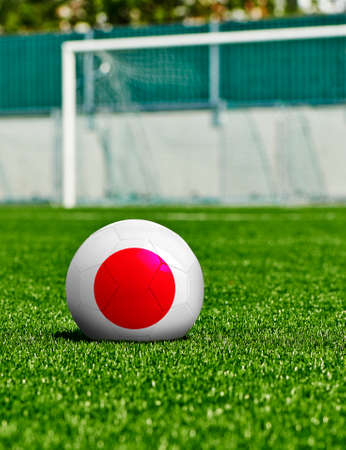 Soccer Ball with Japan Flag on the grass in stadium photo