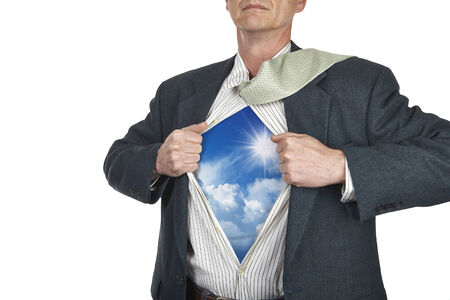 Businessman showing superhero suit underneath his shirt standing against city white background photo
