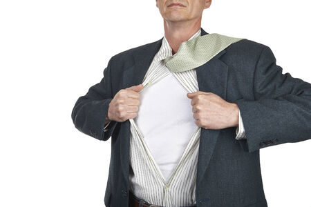 Businessman showing blank superhero suit underneath his shirt standing against city white background photo