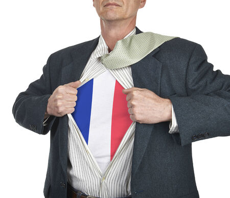 Businessman showing French flag superhero suit underneath his shirt standing against white background photo