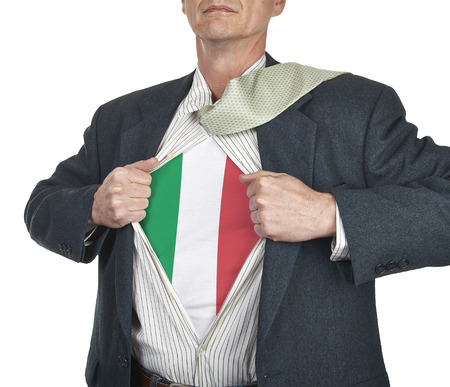 Businessman showing Italy flag superhero suit underneath his shirt standing against white background photo