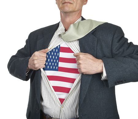 Businessman showing USA flag superhero suit underneath his shirt standing against white background photo