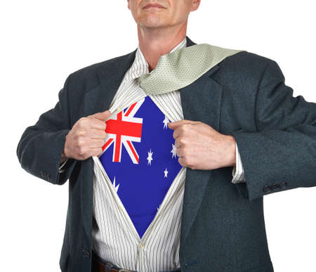 Businessman showing Australia flag superhero suit underneath his shirt standing against white background photo