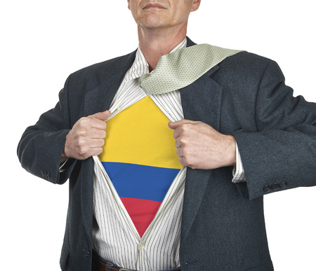 Businessman showing Colombia flag superhero suit underneath his shirt standing against white background photo