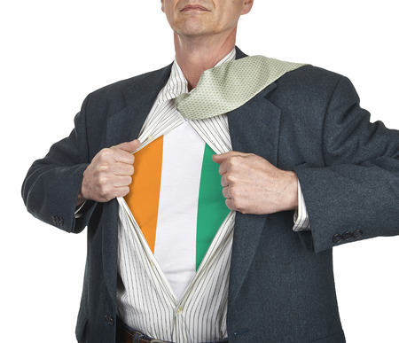 Businessman showing Ivory Coast flag superhero suit underneath his shirt standing against white background photo
