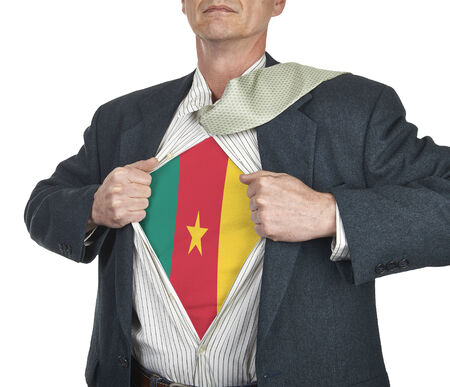 Businessman showing Cameroon flag superhero suit underneath his shirt standing against white background photo
