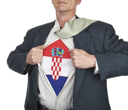 Businessman showing Croatia flag superhero suit underneath his shirt standing against white background photo