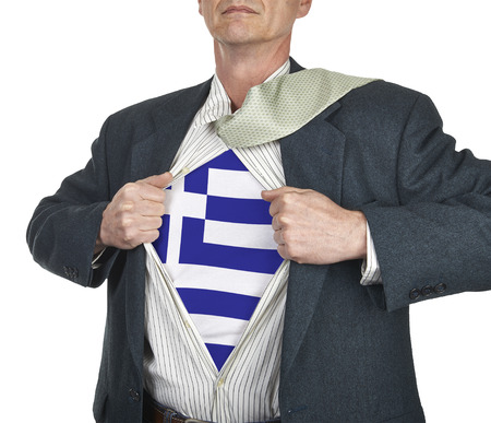 Businessman showing Greece flag superhero suit underneath his shirt standing against white background photo