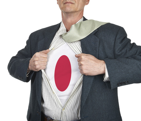 Businessman showing Japan flag superhero suit underneath his shirt standing against white background photo