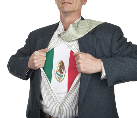Businessman showing Mexico flag superhero suit underneath his shirt standing against white background photo