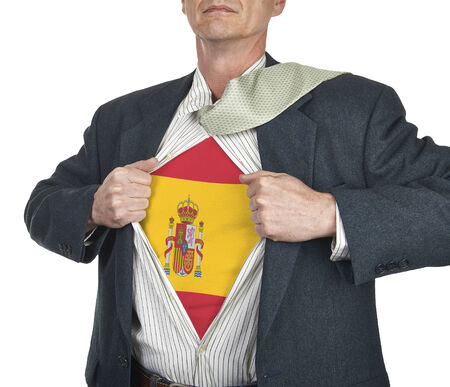 Businessman showing Spain flag superhero suit underneath his shirt standing against white background photo