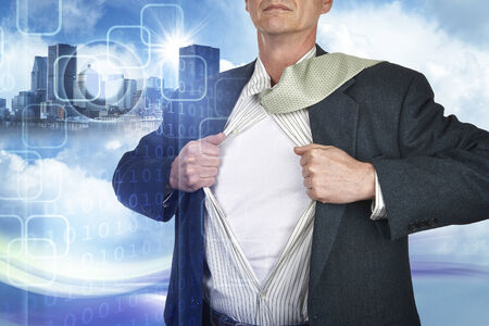 Businessman showing superhero suit underneath his shirt standing against city and technology background photo
