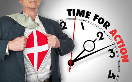 Businessman showing superhero suit with flag from Denmark underneath his shirt standing against clock with time for action - path for the shirt photo