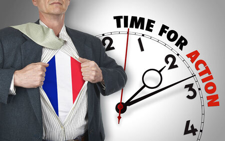 Businessman showing superhero suit with flag from French underneath his shirt standing against clock with time for action - path for the shirt photo