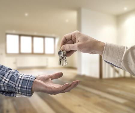 Grundstücksmakler, Hausschlüssel an den Käufer im leeren Raum Lizenzfreie Bilder