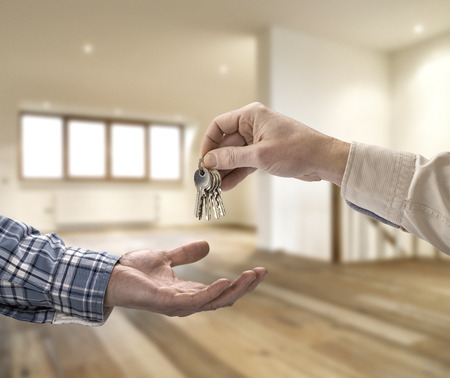 key ring: Realtor giving house key to buyer in empty room Stock Photo