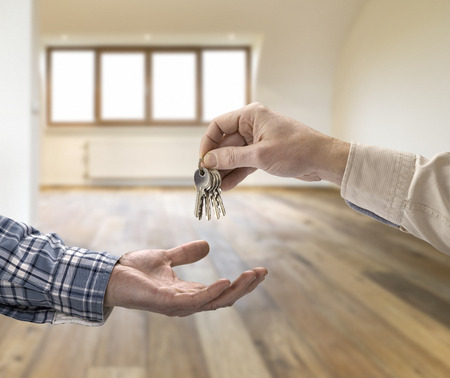 Realtor giving house key to buyer in empty room Фото со стока