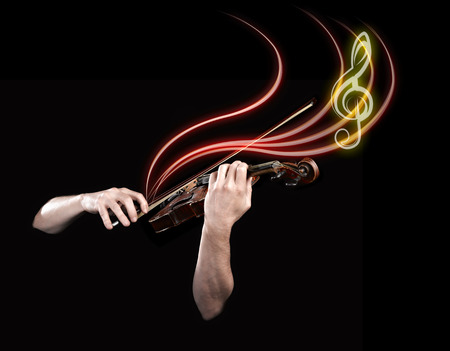 Hands playing  wooden violin with notes flying on black background photo