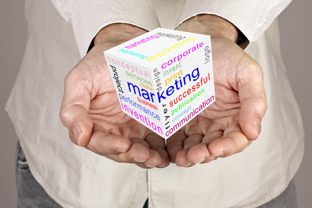 Marketing communication world cube  in male hands photo